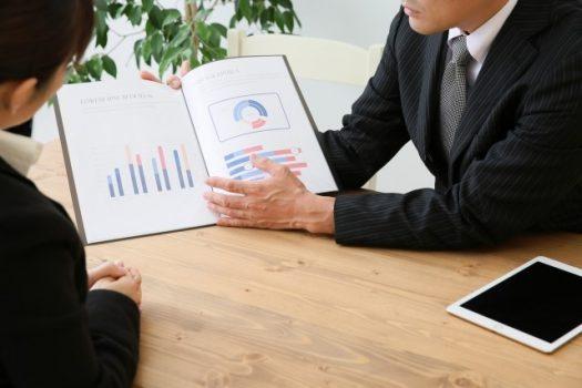 資料を見せて説明するビジネスマン