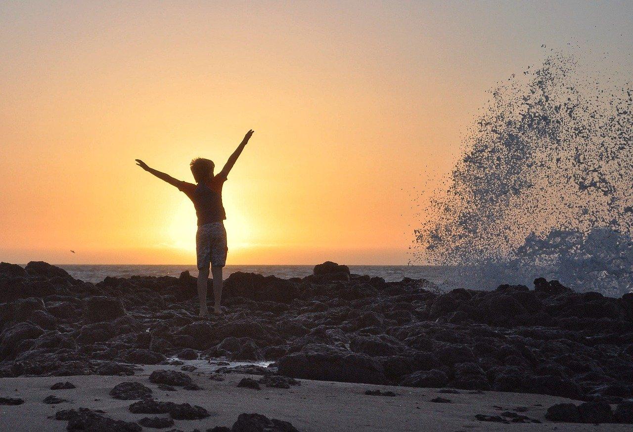海辺で万歳する人