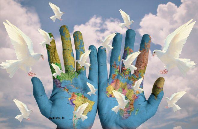 世界地図の描いてある両手から鳩