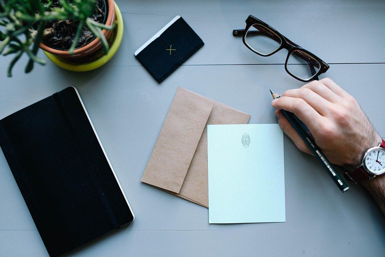 手紙とペンを持つ手