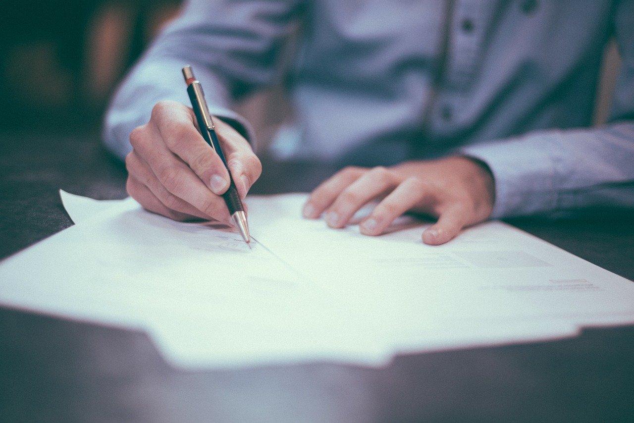ペンで書く男性
