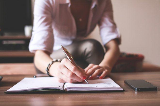 女性がノートに書いている