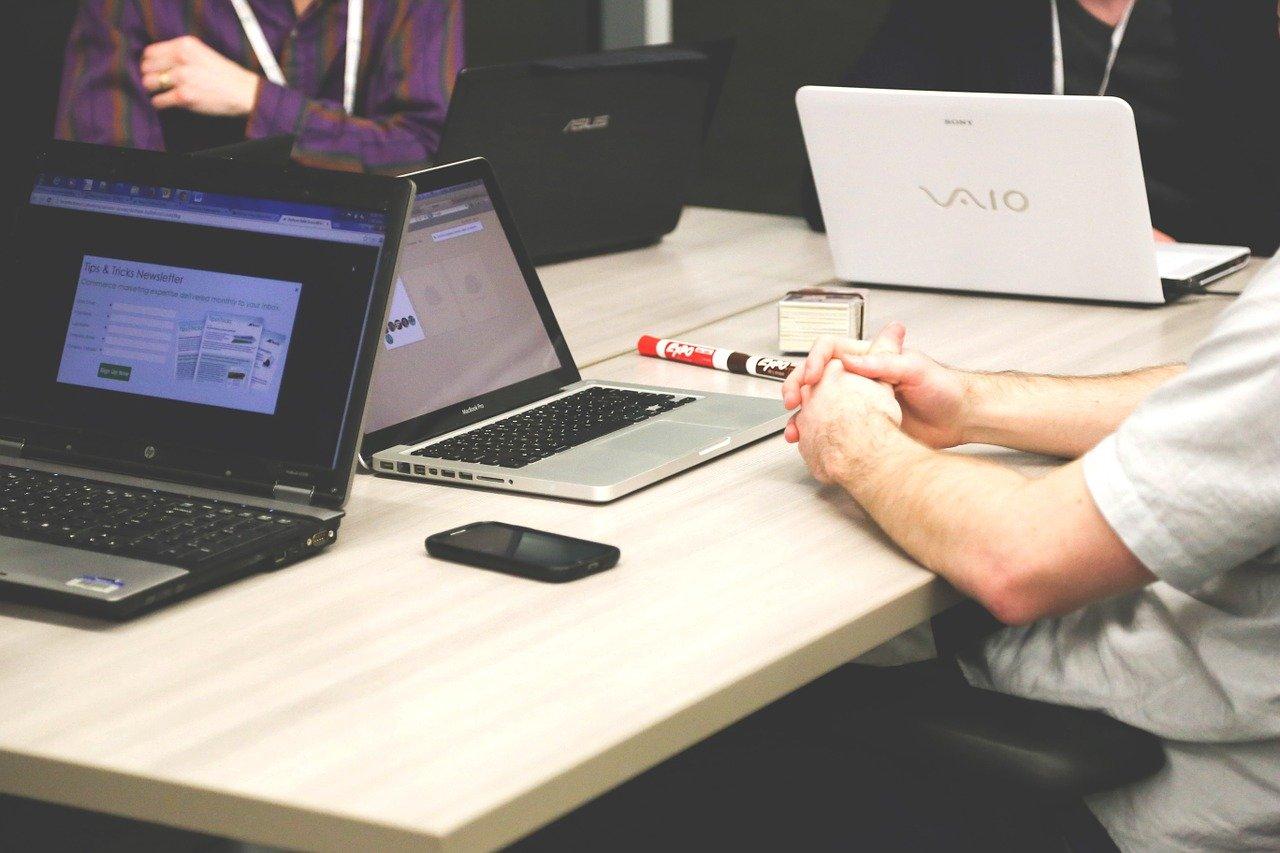パソコンを前に会話する男性たち
