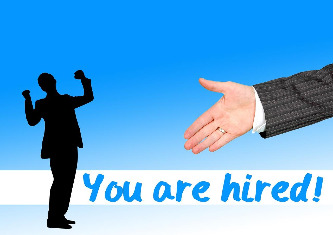 You are hired!の文字の横でガッツポーズする男性の影