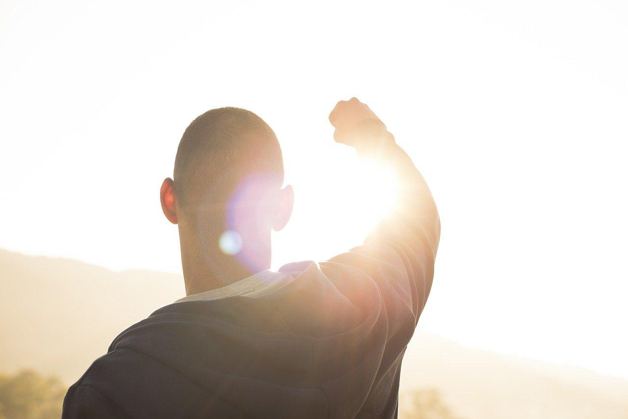 太陽に向かってガッツポーズする男性