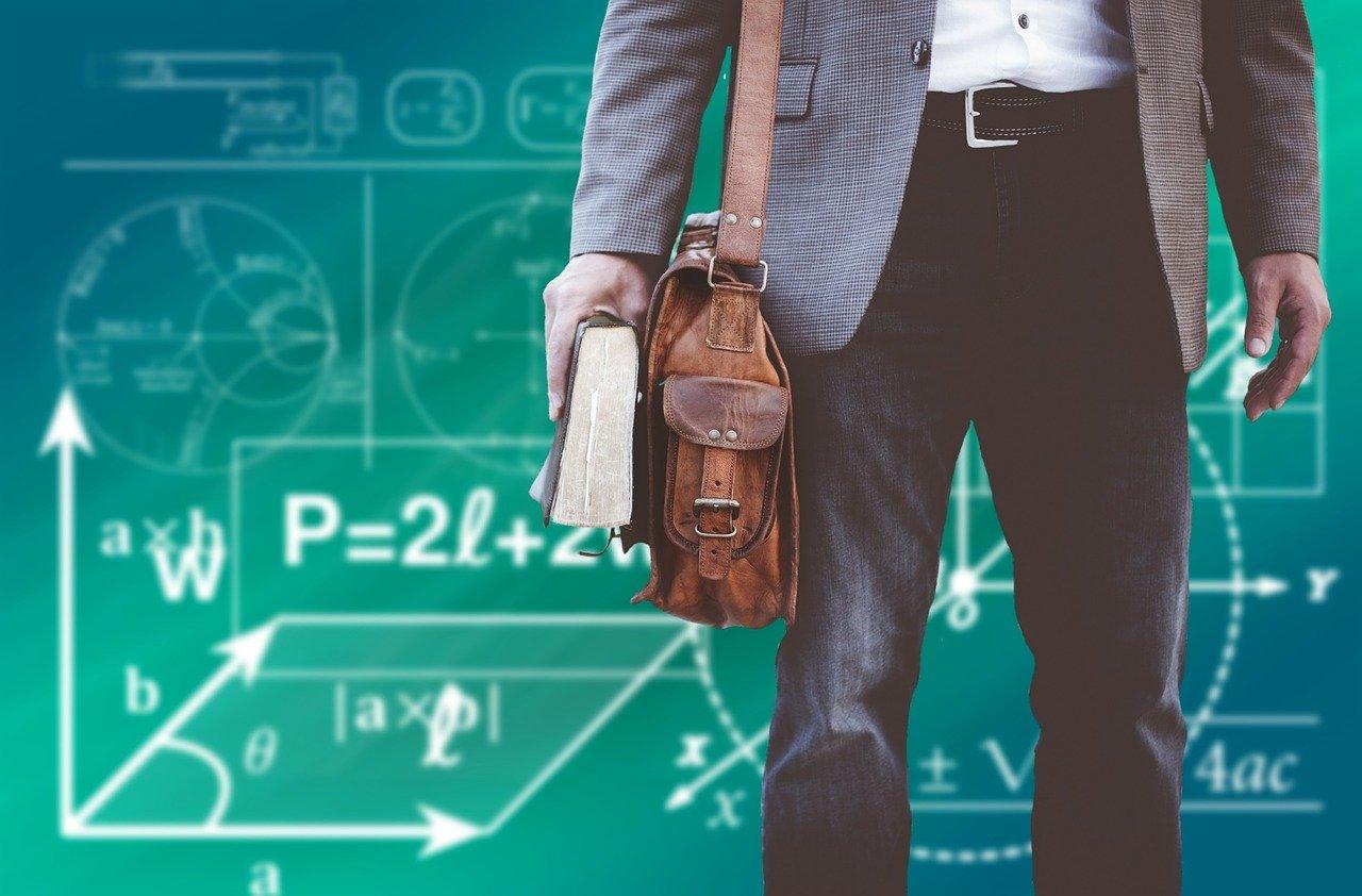 難しい数式が書いてある黒板の前に立つ男性