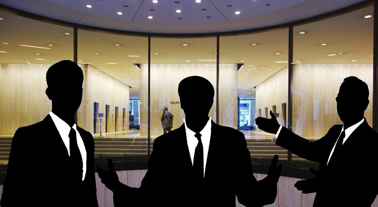 おしゃれなオフィスをバックに、自信ありげにたたずむ3人の男性の影