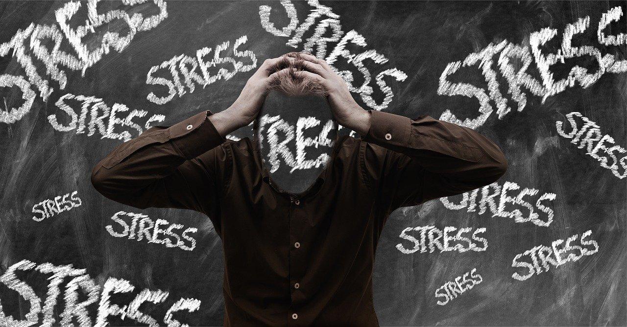 ストレスの文字に囲まれて頭を抱え込む男性