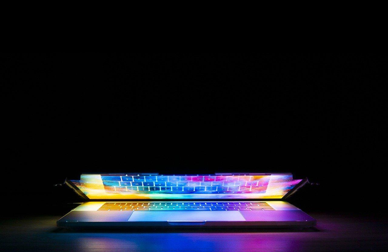少しだけ開かれた、画面が虹色に輝くパソコン