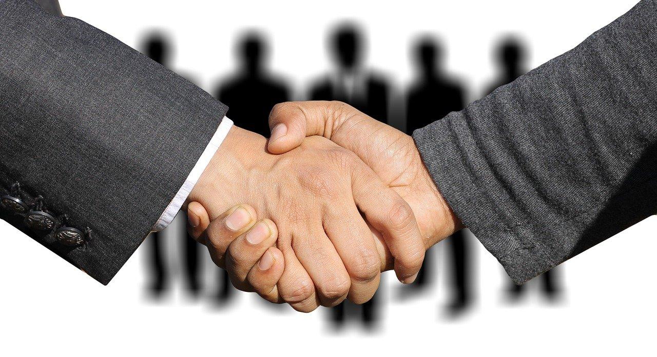 数名の候補者の前で、採用者と握手をする男性の手