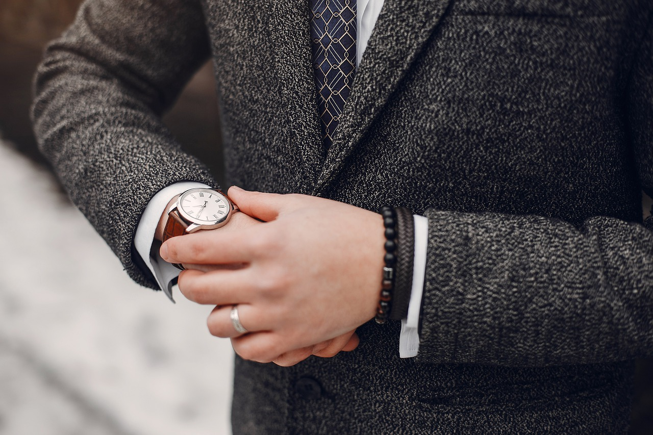 腕時計で時間を確認するスーツの男性