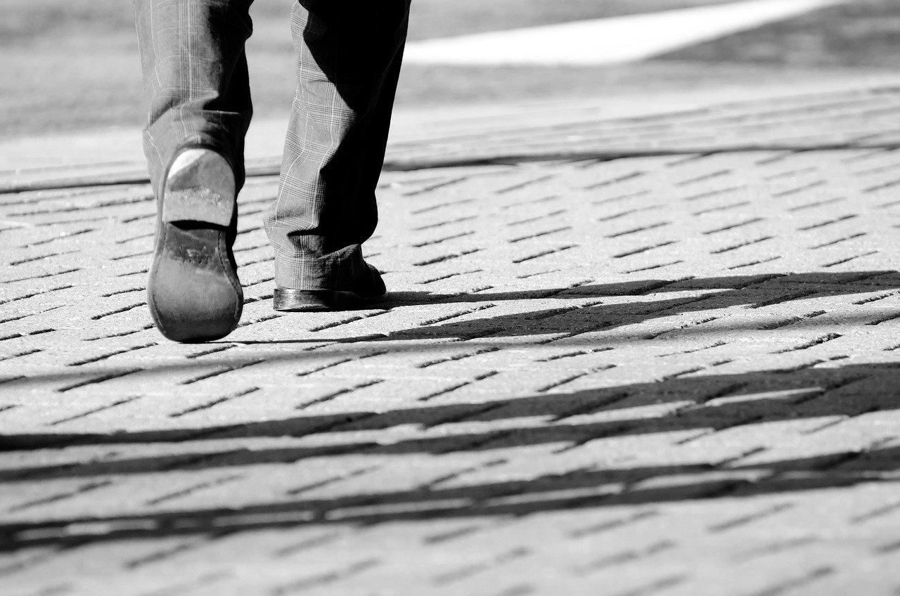 歩いている男性の足のモノクローム写真