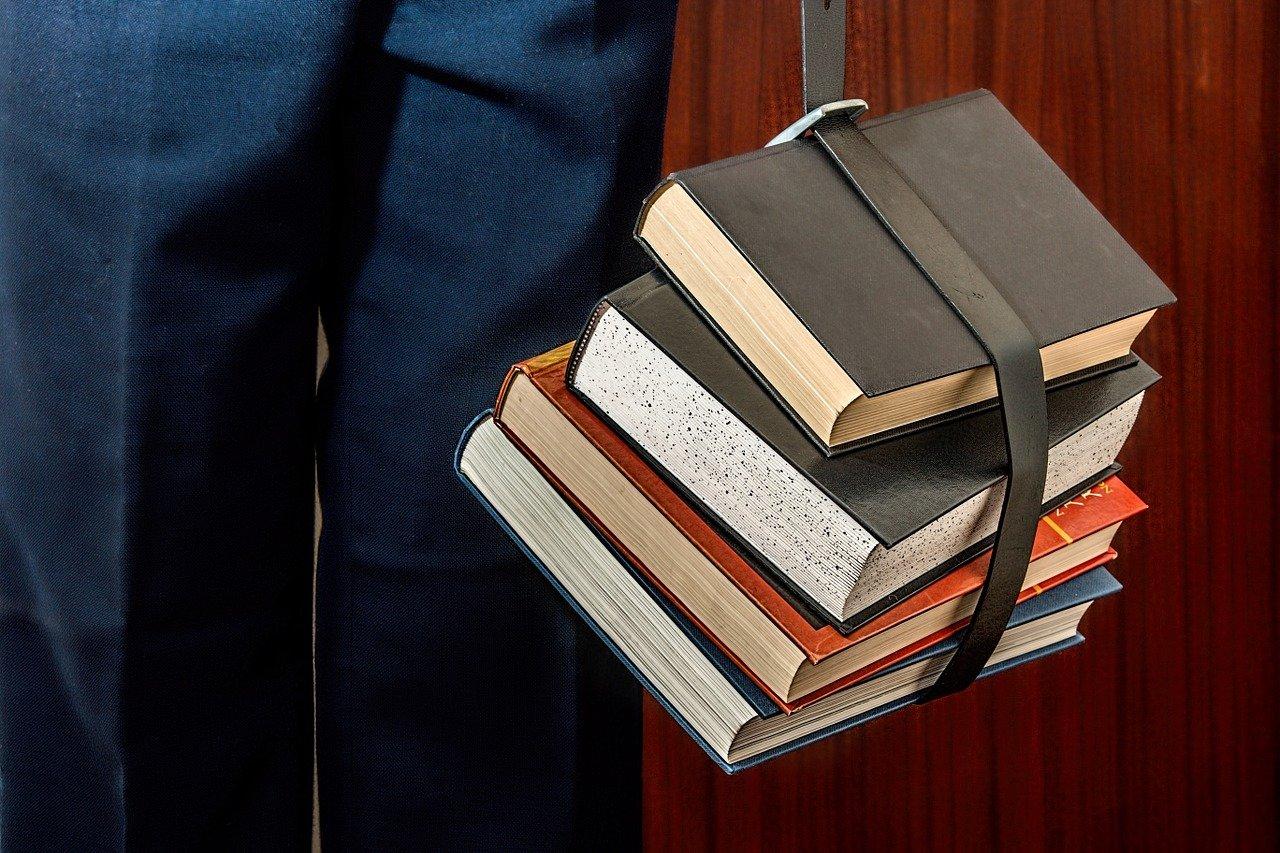 数冊の分厚い参考書を手に提げる男性