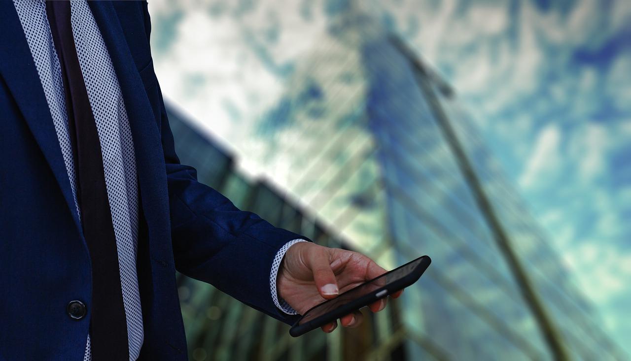 大企業のビルの前でスマホを操作するエリートビジネスマン