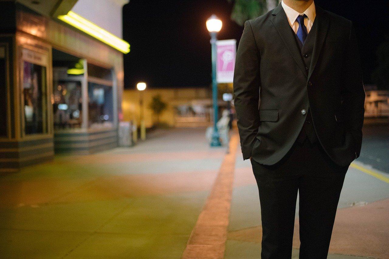 夜の町に一人で佇むスーツの男性