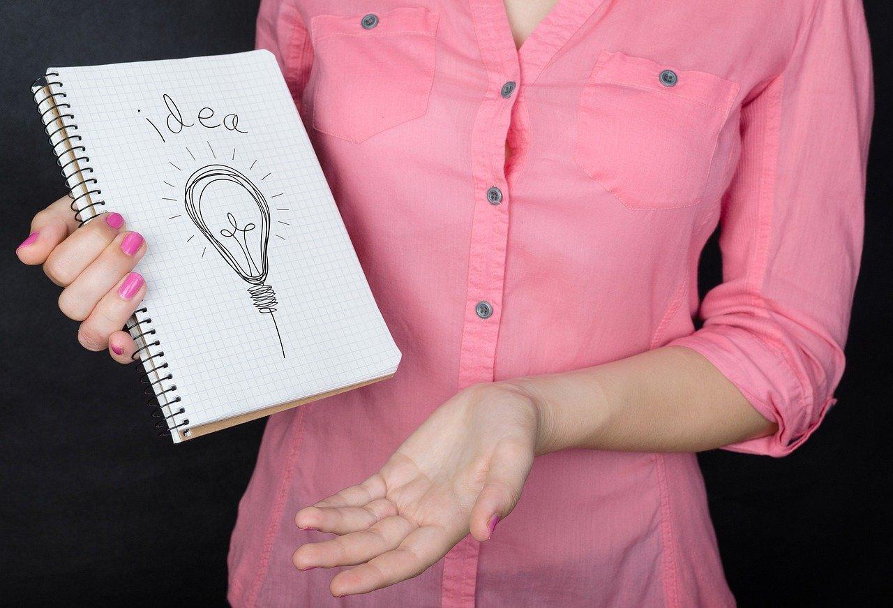 アイディアと書かれたノートを見せる女性