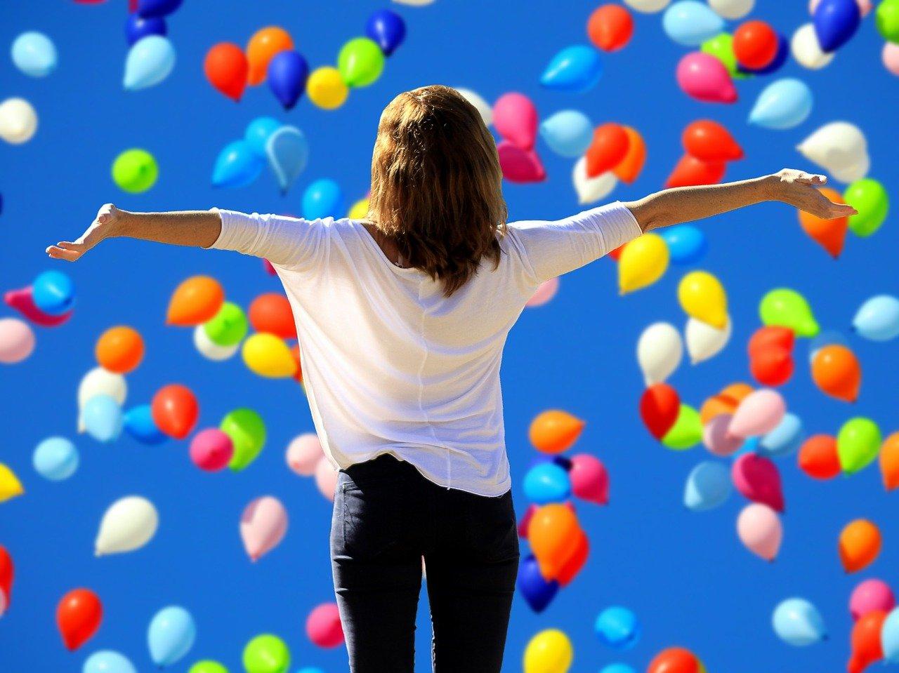空を舞う風船と後姿の女性