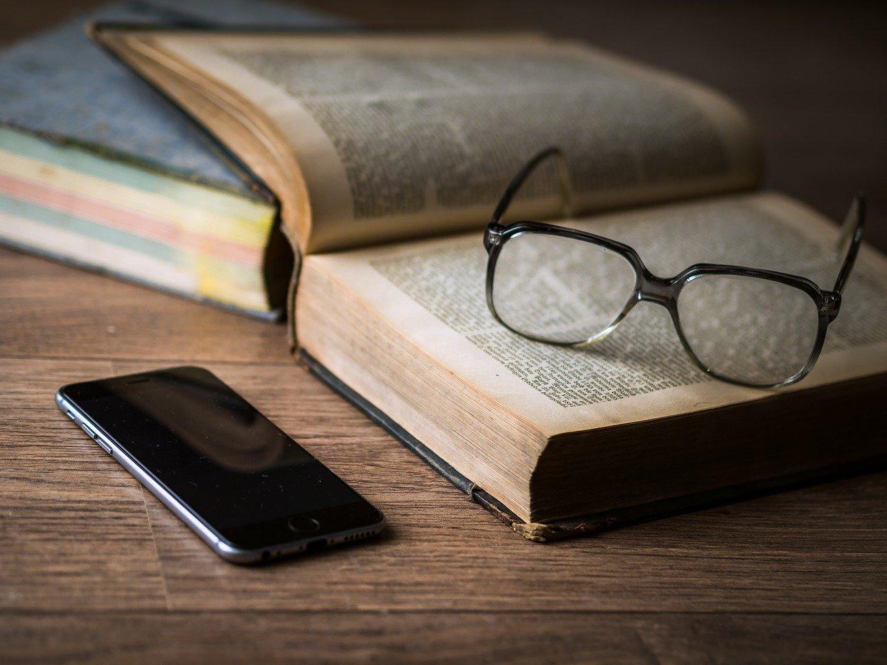 開いた本に置かれたメガネとスマホ