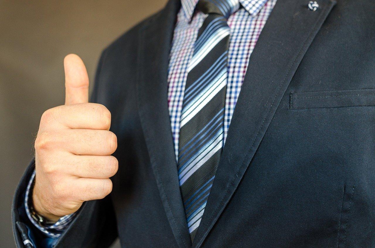 親指を立てて応援しているスーツの男性