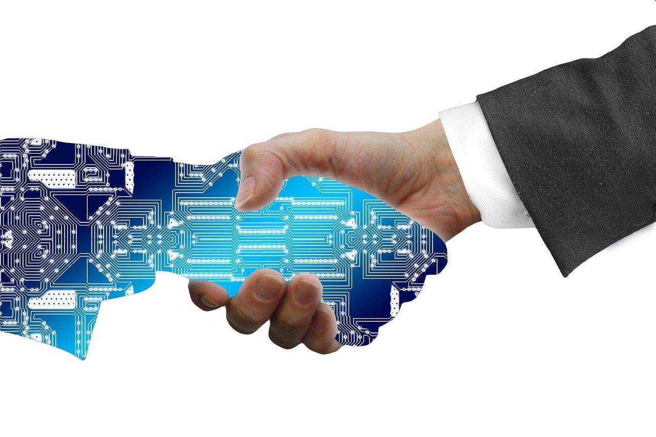 AIの手と握手する人の手