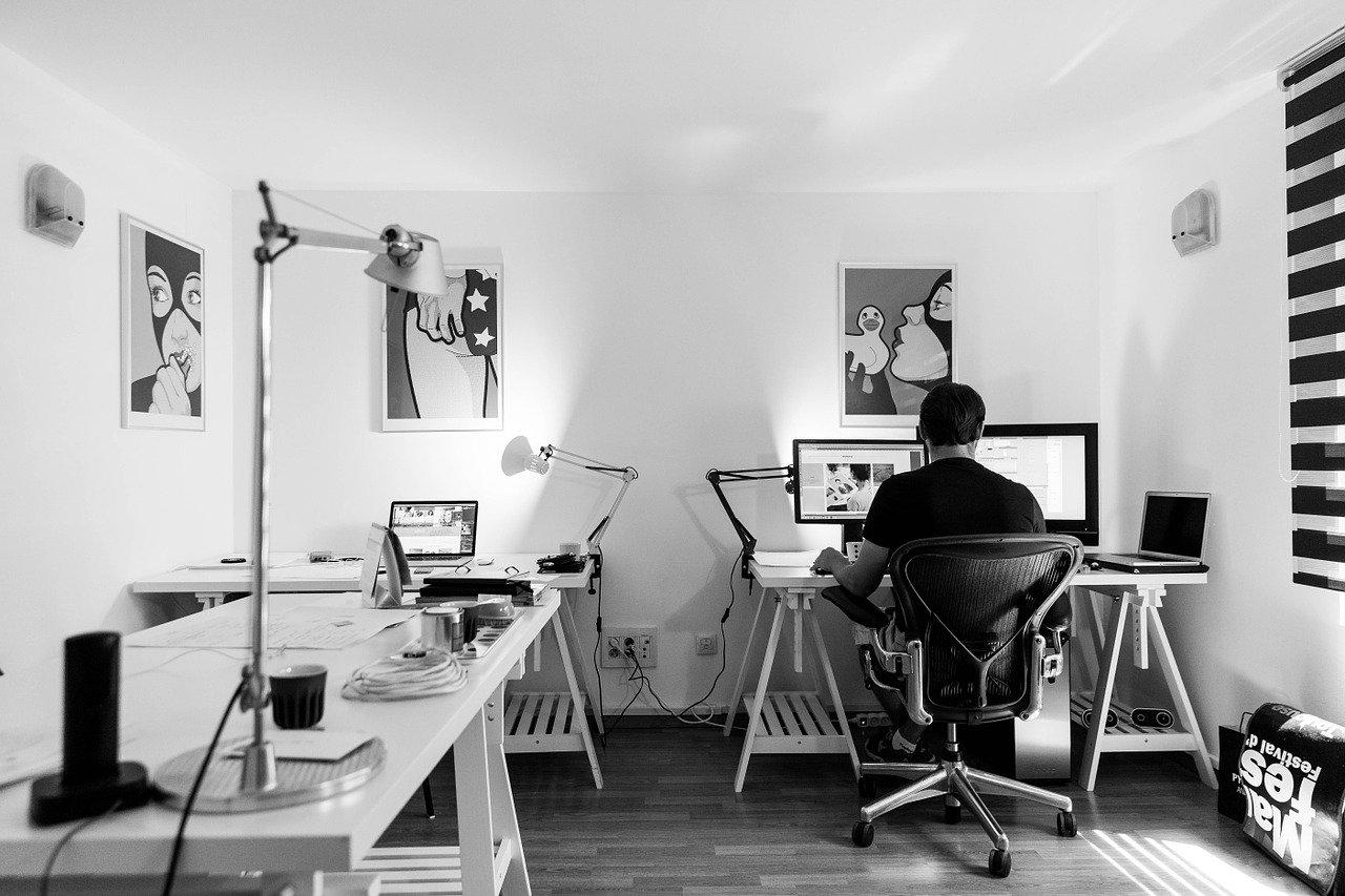 おしゃれなオフィスでデザイン業務をする男性の後ろ姿