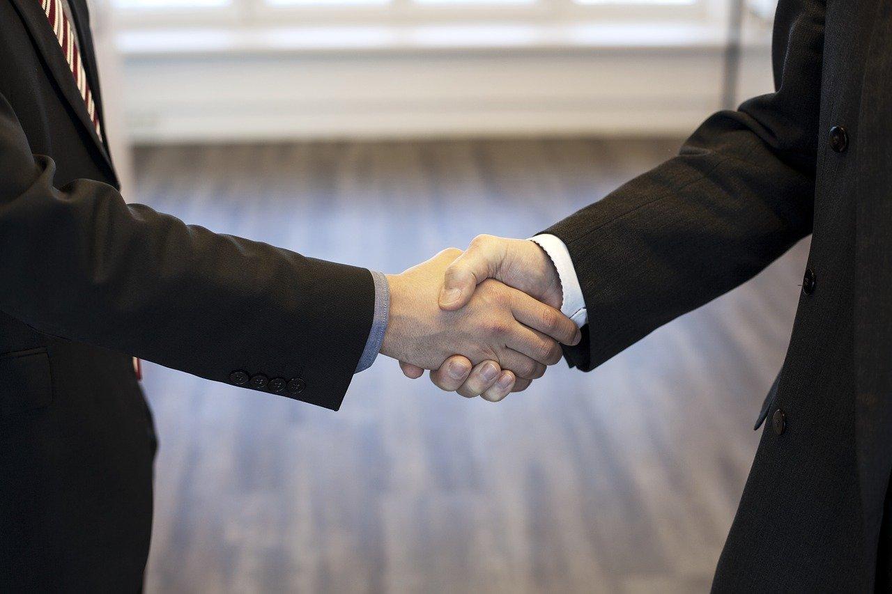 オフィスで握手するスーツの男性たち