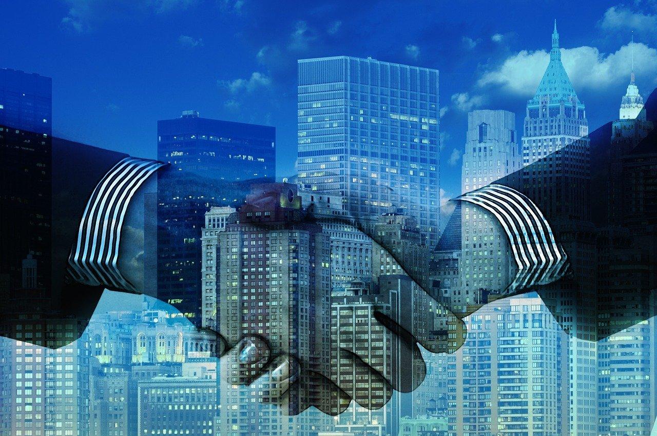 企業のビル群を背景に握手する男性たちの手