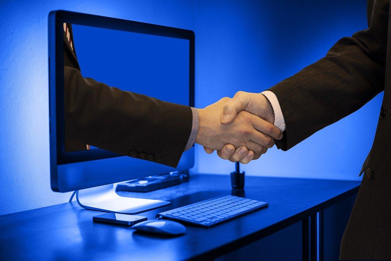 PCの中から出てくる手と握手するスーツの男性