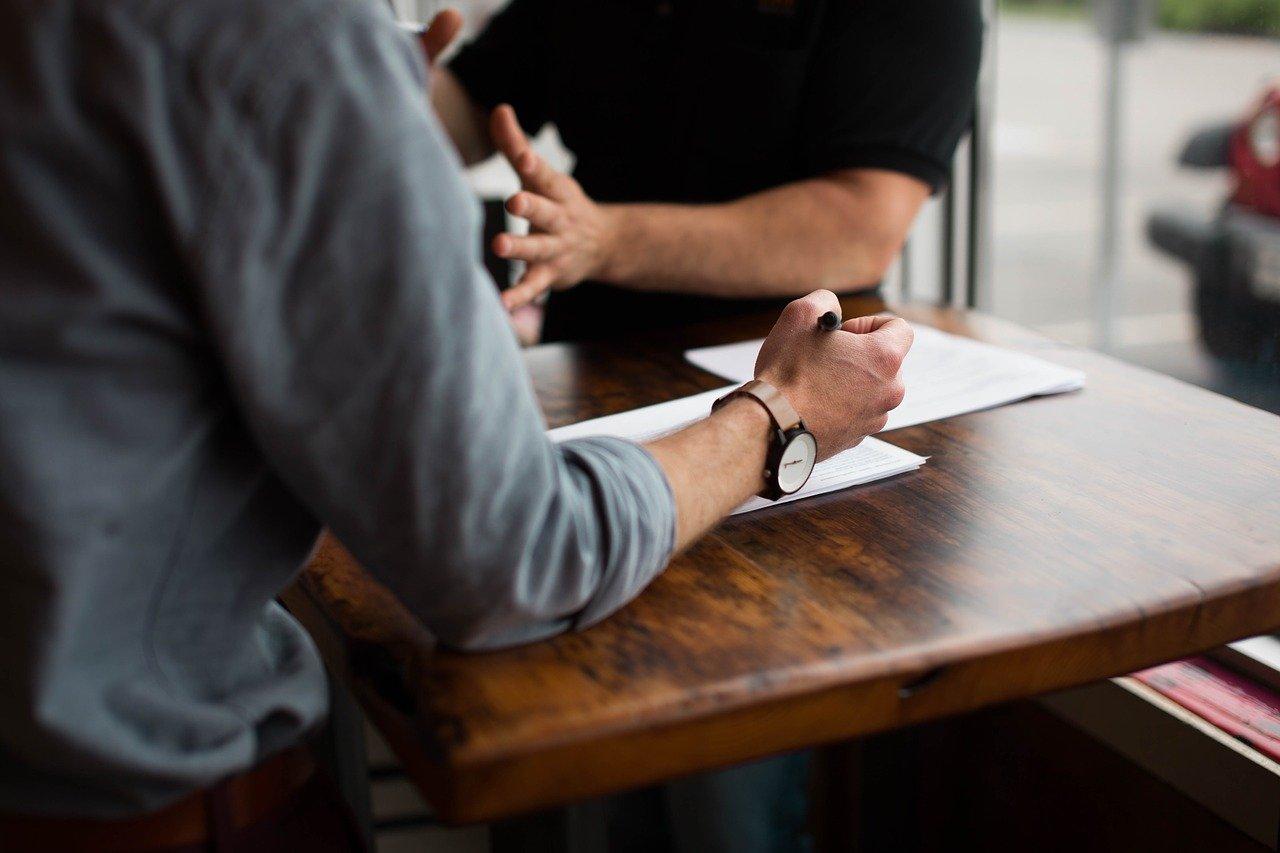 身振り手振りで主張する男性と、それを紙にメモしながら聞く男性