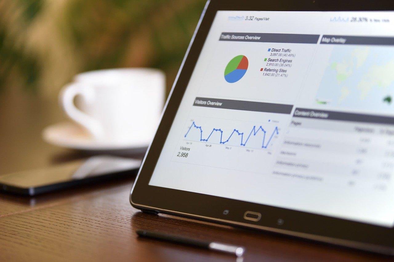PCのデータ分析画面とコーヒーカップ