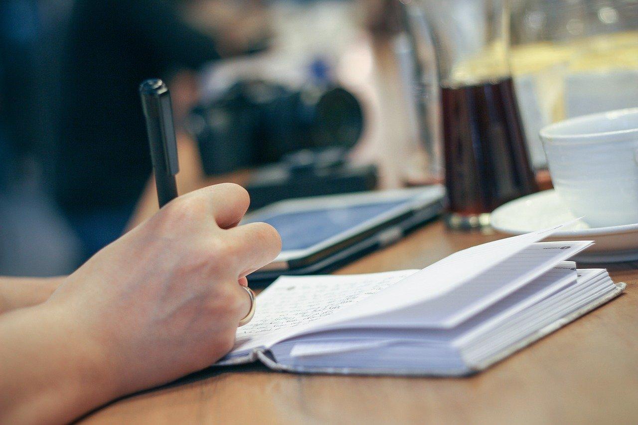 コーヒーを傍らにおいて勉強する人の手