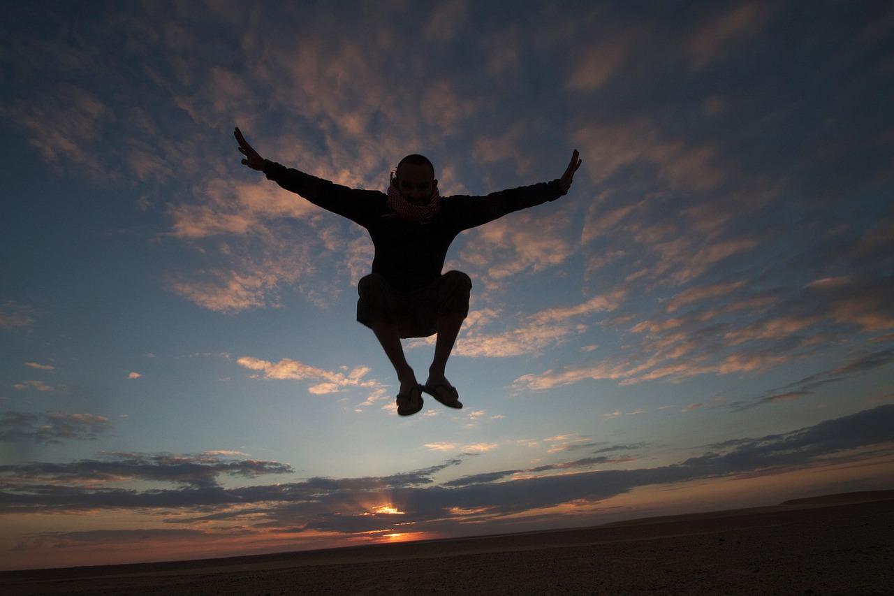 夕方の空をバックにジャンプする男性